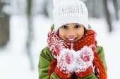 Photo cute african american child showing white snow an smiling at camera in winter forest