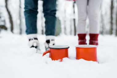 Cropped view of red cups of tea staying in snow in park in snowy forest stock vector