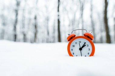 red retro clock standing on white snow near trees in snowy forest