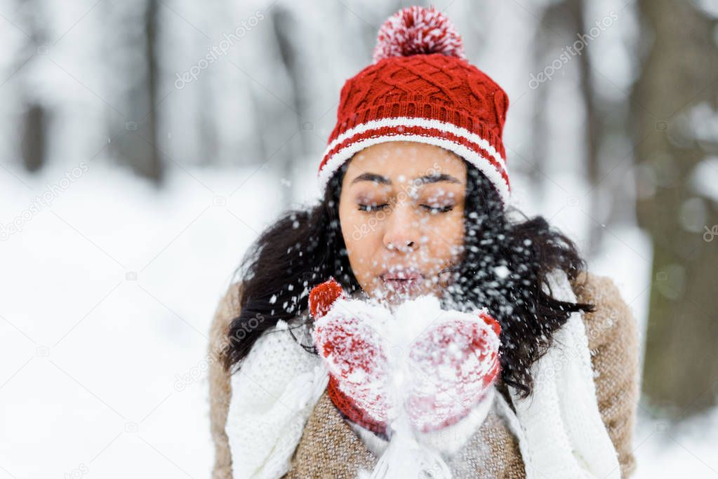 Attractive african american woman blowing snow in park in winter forest stock vector