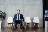 Stilvoller Geschäftsmann sitzt im Rollstuhl in Wartehalle und blickt in die Kamera
