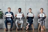 mnohonárodnostní podnikatelé drží karty s milencem, ředitel, vypálil slova a otazník v čekací hale