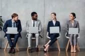 s úsměvem mnohonárodnostní podnikatelé sedí na židlích a používání notebooků v čekací hale