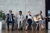 Fotografie multiethnic businesspeople sitting, using digital devices and playing acoustic guitar in waiting hall