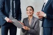 usmívající se asijské podnikatelka drží složku během setkání s kolegy v kanceláři