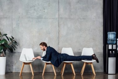 businessman lying on chairs and using laptop in waiting hall