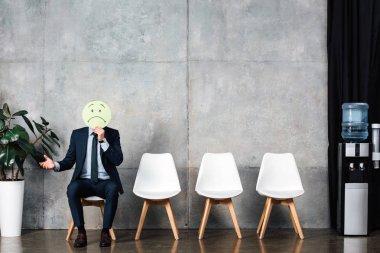 businessman in suit sitting on chair and holding card with sad face expression in waiting hall