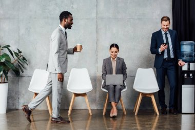 smiling multiethnic businesspeople with digital devices and coffee in waiting hall