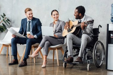 multicultural businesspeople sitting and listening while disabled african american man playing guitar in waiting hall