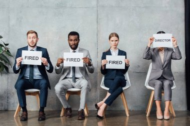 multiethnic businesspeople sitting and holding cards with 'fired' and 'director' words in waiting hall