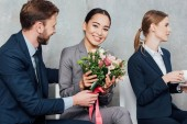Fotografie businessman presenting flowers to beautiful smiling asian businesswoman in office