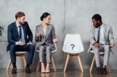 překvapený mnohonárodnostní podnikatelé při pohledu na kartu s otazníkem na židle do čekárny