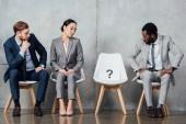 mnohonárodnostní podnikatelé při pohledu na kartu s otazníkem na židle do čekárny