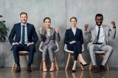 lächelnd multiethnischen Geschäftsleute sitzen auf Stühlen und jubeln mit geballten Fäusten in der Wartehalle