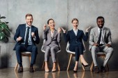 Fotografie happy multiethnic businesspeople sitting on chairs and cheering with clenched fists in waiting hall