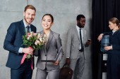 Fotografie smiling businessman presenting flowers to businesswoman with multiethnic colleagues on background in waiting hall