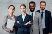 Fotografie focused multiethnic group of businesspeople in formal wear posing and looking at camera
