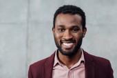 portrét s úsměvem africké americké neformální podnikatel na šedém pozadí