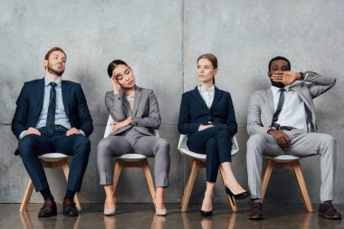 bored multiethnic businesspeople sitting on chairs in waiting hall