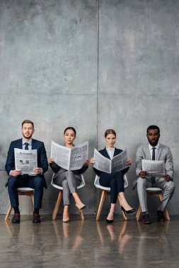 serious multiethnic businesspeople sitting on chairs and reading newspapers in waiting hall