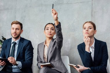 focused businesswoman raising hand while having meeting with colleagues in office