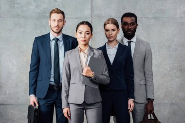 focused multiethnic group of businesspeople in formal wear posing and looking at camera