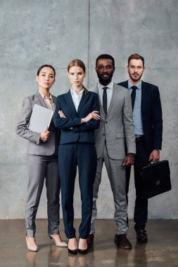 concentrated multiethnic group of businesspeople in formal wear looking at camera and posing