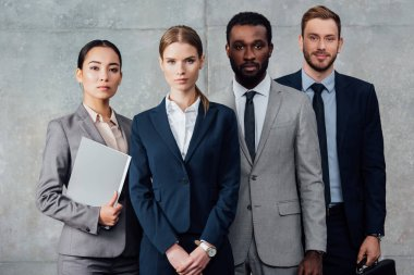 serious multiethnic group of businesspeople in formal wear posing and looking at camera