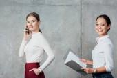 többnemzetiségű alkalmi üzletasszonyok, beszél a smartphone és a gazdaság mappát a dokumentumok office