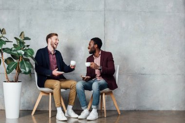 happy multiethnic men sitting, drinking coffee and talking in waiting hall
