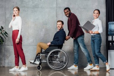 smiling multiethnic group of people in casual clothes rolling man in wheelchair in waiting hall
