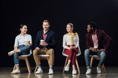 smiling multiethnic group of people in casual clothes sitting on chairs with coffee to go isolated on black