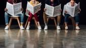 mnohonárodnostní skupiny příležitostné podnikatelé sedí na židlích a obchodní noviny