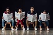 többnemzetiségű csoport székeken ülnek, és az olvasás üzleti újságok elszigetelt fekete alkalmi üzletemberek