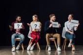 Fotografia Gruppo multietnico di gente seduta e si tengono carte con regista, licenziato parole e punti interrogativi isolati sul nero