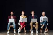 többnemzetiségű csoport mosolygó alkalmi üzletemberek székeken ülnek, és használ a laptops elszigetelt fekete