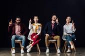 Fotografia Gruppo multietnico di persone seduti su sedie e mostrando gesti idea isolati sul nero