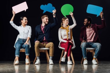 happy multiethnic people holding speech bubbles and thought bubble isolated on black