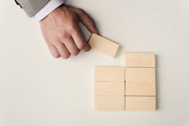 Cropped view of man holding brick in hand near wooden blocks symbolizing building success isolated on white stock vector