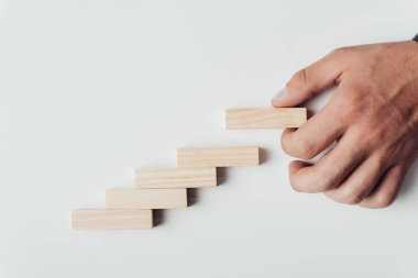 cropped view of man putting wooden brick on top of wooden blocks symbolizing career ladder isolated on white