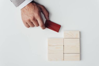 cropped view of man holding red brick in hand near wooden blocks symbolizing building success isolated on white