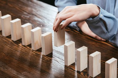 selective focus of woman picking wooden brick from row of blocks on desk