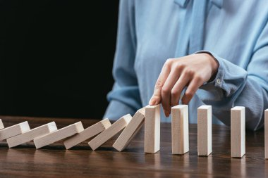 partial view of woman sitting at desk and preventing wooden blocks from falling isolated on black