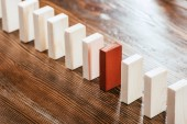 selective focus of wooden block row with red one on desk