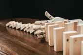 Fotografie robotic hand preventing wooden blocks from falling on desk isolated on black