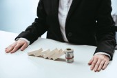 Photo cropped view of businesswoman sitting at table with fallen row of wooden blocks and money roll