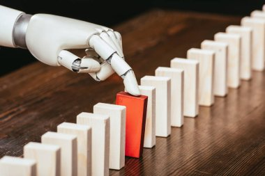 robotic hand picking red wooden brick from row of blocks on desk