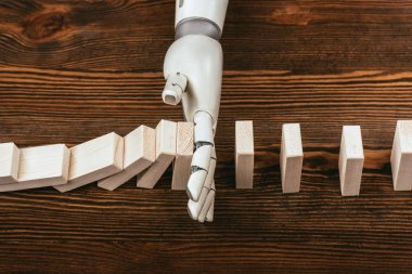robotic hand preventing wooden blocks from falling on desk