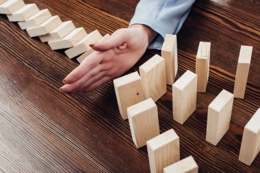 partial view of woman preventing wooden blocks from falling at desk