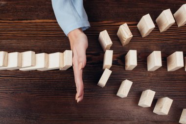 cropped view of woman preventing wooden blocks from falling at desk